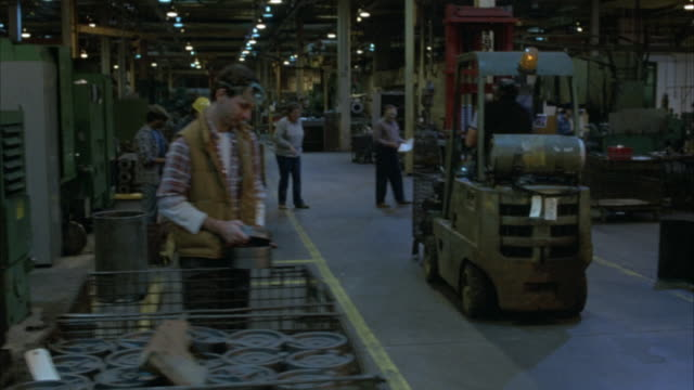 CLOSE ANGLE OF BACK OF FORKLIFT. SHOT PULLS BACK, SEE MEDIUM ANGLE OF WORKERS ON FACTORY FLOOR. WORKERS MAINLY WHITE MALES WEARING WORK SHIRTS AND HARDHATS.