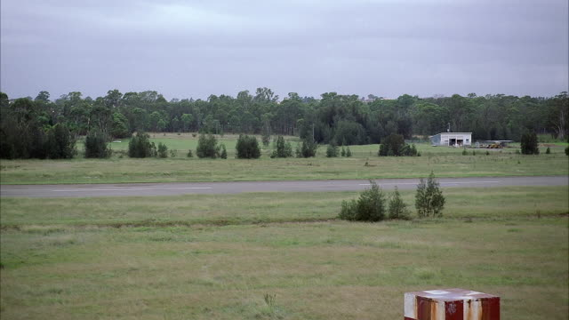 MEDIUM ANGLE GREEN, GRASSY AREA IN FOREGROUND, FIR TREES IN BACKGROUND, AIRPLANE RUNWAY BETWEEN. SEE SHACK IN BACKGROUND.