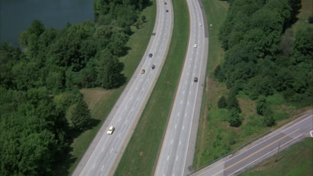 AERIAL BIRDSEYE POV OF HIGHWAY OR FREEWAY IN COUNTRYSIDE. FEW CARS DRIVING ON FREEWAY. SEE GRASSY MEDIAN, MANY TREES SURROUNDING FREEWAY, AND LAKE OR RIVER TO LEFT OF SHOT. SHOT PANS UP AND ZOOMS IN ON FREEWAY BY END OF SHOT.