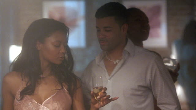 MEDIUM ANGLE. CAMERA PANS RIGHT TO LEFT TO TWO WOMEN DANCING TOGETHER WITH A MAN IN NIGHTCLUB. BOTH FEMALES ARE HOLDING DRINKS WHILE DANCING. MALE LOOKS AT WATCH, KISSES FEMALES, AND LEAVES.