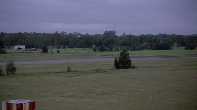 MEDIUM ANGLE GREEN, GRASSY LANDSCAPE IN FOREGROUND, FIR TREES IN BACKGROUND, AIRPLANE RUNWAY BETWEEN. SEE SHED AND EQUIPMENT IN BACKGROUND.