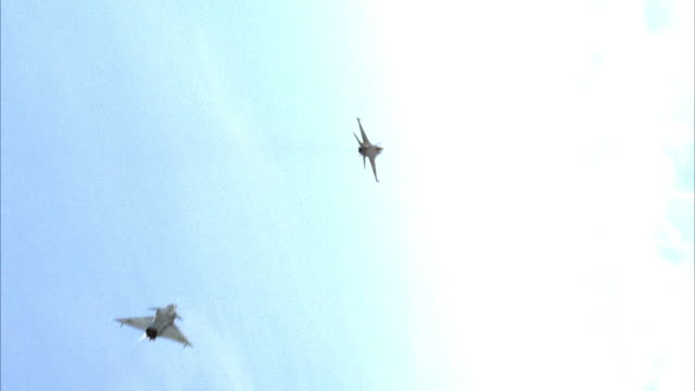 TRACKING SHOT OF F-16 FIGHTER JET FOLLOWED BY KFIR JET FLYING AWAY FROM CAMERA.  BOTH  MAKE BANKED RIGHT TURNS FOLLOWED BY RIGHT BARREL ROLLS AND FLY VERTICAL.