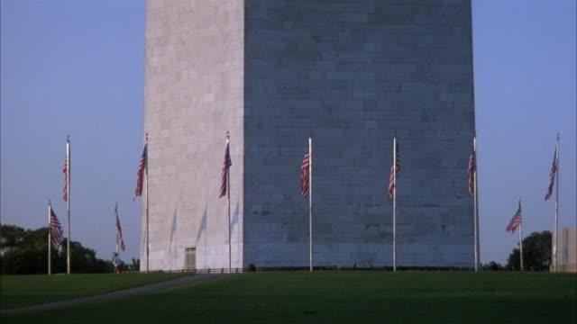 ESTABLISHED MEDIUM ANGLE OF BASE OF WASHINGTON MONUMENT WITH AMERICAN FLAG POLES SURROUNDING BASE. GRASS ON GROUND.