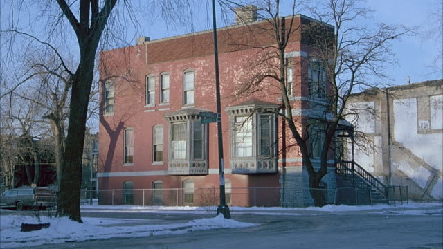 MEDIUM ANGLE OF SIDE OF BROWNSTONE APARTMENT BUILDING ON STREET CORNER. SNOW ON GROUND AND BARE TREES.