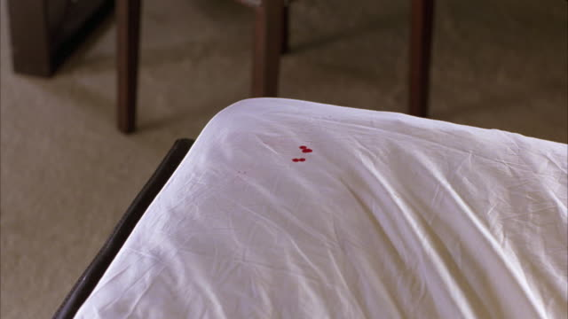 CLOSE ANGLE OF BLOOD DROPS FALLING ONTO WHITE LINENS OR BLANKETS OF CORNER OF BED IN BEDROOM OR HOTEL ROOM. COULD BE CRIME SCENE.