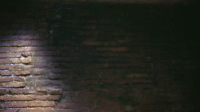 MEDIUM ANGLE OF BRICK WALL. BODY AND DEBRIS FALL FROM ABOVE, FALLING THROUGH FRAME IN A FLURRY OF DUST.