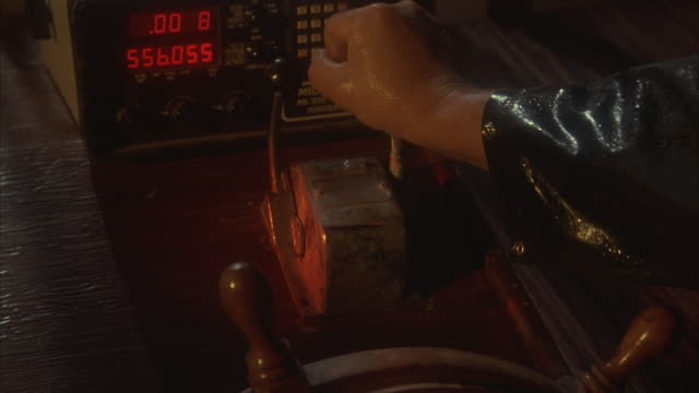 CLOSE ANGLE OF SHIP'S BRIDGE, CONTROL ROOM. SEE TOP OF WOODEN STEERING WHEEL AND TWO LEVERS ABOVE. DIGITAL READOUT ON MACHINE WITH BUTTONS. MAN'S HAND, ARM IN BLACK RAINCOAT WORKS TO PUSH LEVERS FORWARD.
