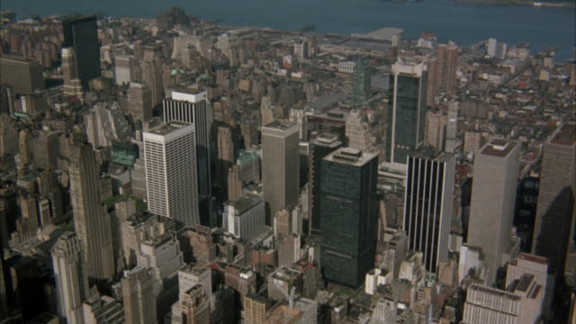 AERIAL OF MIDTOWN MANHATTAN. SEE SKYSCRAPERS AND HIGH RISES, RIVER AT TOP OF SHOT. ENDS ON FOCUS OF EMPIRE STATE BUILDING, THEN BLOCK OF SMALLER BUILDINGS.