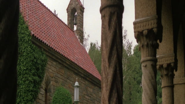 MEDIUM ANGLE OF SIDE OF CHURCH OR BRICK BUILDING WITH RED TILE ROOF. BELL TOWER ON SIDE. COLUMNS IN FOREGROUND, TREES IN BACKGROUND.