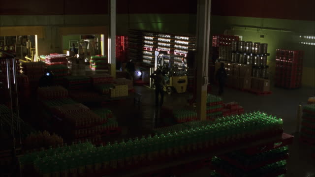 WIDE ANGLE OF INTERIOR OF SODA BOTTLE WAREHOUSE. SEE STACKS OF SODA BOTTLES AND SODA CANS. SEE MEN DRESSED ALL IN BLACK WITH GUNS AND FLASHLIGHTS ROAMING AROUND WAREHOUSE.
