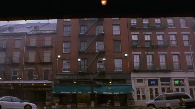 WIDE ANGLE OF MULTI STORY RED BRICK APARTMENT BUILDING WITH FIRE ESCAPE. POV FROM ACROSS STREET. FULTON FISH MARKET. COULD BE USED FOR BRONX, QUEENS, OR BROOKLYN WATERFRONT.