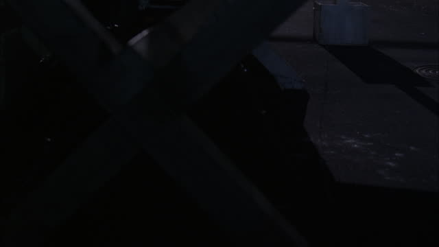 MEDIUM ANGLE OF ALLEY BETWEEN BRICK BUILDINGS. BLACK SEDAN DRIVING UNDER CHECKPOINT GATE ARM WHICH ARMY SOLDIER RAISES.