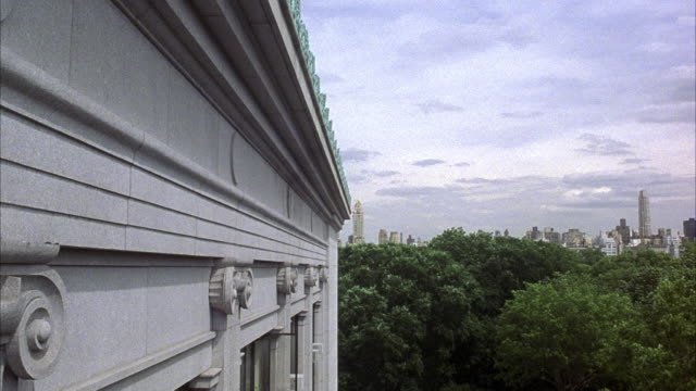 CLOSE ANGLE. CAMERA MOUNTED UNDERNEATH ROOF OVERHANG LOOKING DOWN SIDE OF ROMAN STYLE HIGH RISE BUILDING. SEE CENTRAL PARK AND DOWNTOWN IN BACKGROUND.