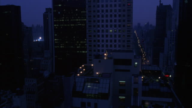 MEDIUM ANGLE OF DOWNTOWN NEW YORK CITY. SEE SURROUNDING HIGH RISE BUILDINGS AT LATE DUSK. POV FROM ROOFTOP OF HIGH RISE.