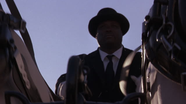 UP ANGLE OF A HANSOM CABBIE ON A HORSE DRAWN CARRIAGE.  THE DRIVER WEARS A BOWLER HAT, WHITE GLOVES, AND A BLACK SUIT. HE HOLDS THE REINS IN HIS HANDS, AND HE GUIDES THE TWO WHITE HORSES. MATCHES WIDER SHOTS OF FUNERAL.