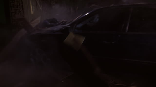 TRACKING SHOT OF SPEEDING BMW CAR OUTSIDE LOWER CLASS HOTEL OR MOTEL. STUNT MAN HANGING UPSIDE DOWN OUT OF SUNROOF. CAR CRASHES INTO BUILDING.