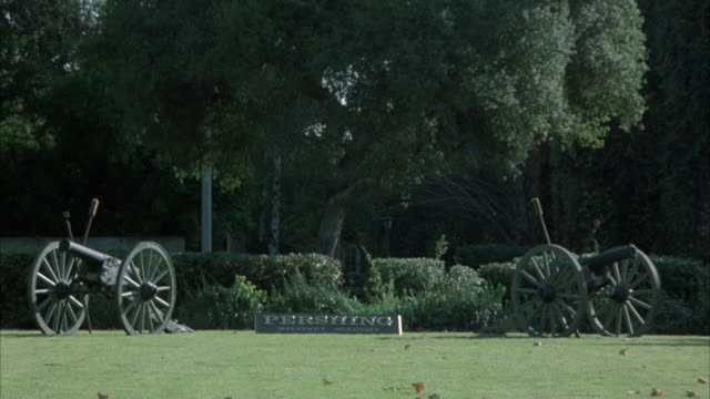 MEDIUM ANGLE OF PERSHING MILITARY BASE SIGN WITH TWO SURROUNDING CANNON STATUES ON LAWN. SEE TREES AND PLANTS IN BG. ZOOMS OUT A LITTLE AT END.