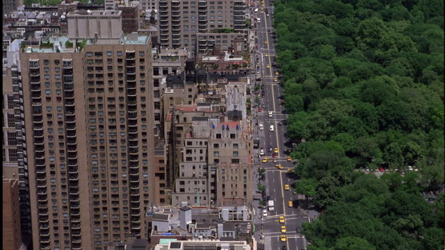 WIDE ANGLE ON HIGH RISE BUILDINGS ON THE EAST SIDE OF MANHATTAN. SEE TREETOP IN CENTRAL PARK ACROSS STREET FROM BUILDINGS. PANS UP. SEE DOWNTOWN AREA AND CENTRAL PARK WITH CITY STREET DIVIDING THE MIDDLE.