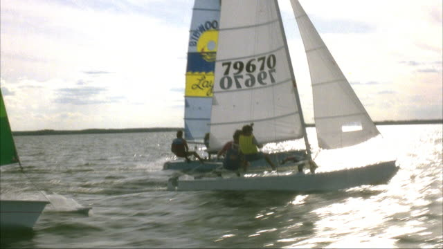 MEDIUM ANGLE SIDE MOVING POV OF HANDFUL OF SAILBOATS OR CATAMARANS SAILING TO RIGHT ACROSS BODY OF WATER OR LAKE. SAILBOATS HAVE LOGOS OF SPONSORS. MOST LIKELY DURING A RACE.