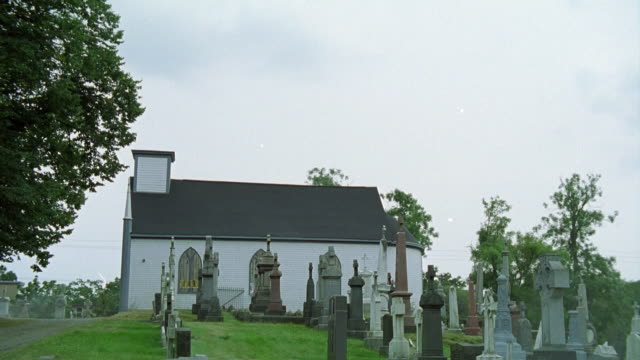 WIDE ANGLE OF CHURCH OR CHAPEL ON HILLTOP NEXT TO GRAVEYARD OR CEMETERY. HEADSTONES AND TOMBSTONES VISIBLE.