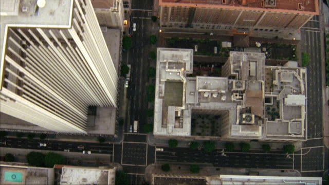 AERIAL BIRDSEYE POV OF DOWNTOWN LOS ANGELES. SEE ROOFTOPS OF BUILDINGS ALONG VERTICAL CITY STREET.