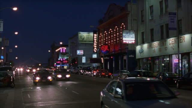 WIDE ANGLE OF BROADWAY STREET IN NORTH BEACH. SEE STOREFRONT. SEE MARQUEE THAT SAYS BROADWAY ACROSS STREET. CARS DRIVING TOWARD CAMERA ON STREET. NIGHTCLUBS, STRIP CLUBS.