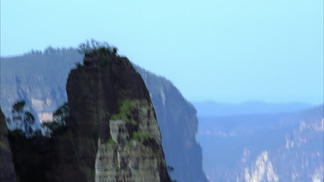 MEDIUM ANGLE OF ROCK MOUNTAIN OR CLIFF. SEE POV PAN DOWN FROM TOP OF MOUNTAIN TO VALLEY BELOW. SEE SCATTERED GREEN TREES AND VEGETATION. SEE  VERTICAL, SMOOTH SIDES OF ROCK STRUCTURE. SEE HAZY SKY.