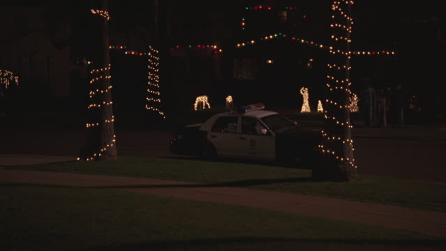 WIDE ANGLE OF POLICE CAR PARKED NEXT TO CURB IN SUBURBAN NEIGHBORHOOD. CHRISTMAS LIGHTS DECORATE HOUSE IN BG AND PALM TREES. CHRISTMAS DECORATIONS VISIBLE ON LAWN.