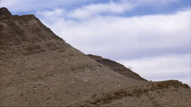 MEDIUM ANGLE OF DESERT MOUNTAIN. SEE SCATTERED SHRUBS ON SIDE OF MOUNTAIN. SEE BLUE SKY WITH CUMULUS CLOUDS IN BACKGROUND. COULD BE MIDDLE EAST, IRAN, IRAQ, OR NEVADA.
