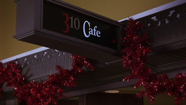 PAN DOWN FROM A SIGN READING 310 CAFE TO A WOMAN AT A TABLE STIRRING A DRINK.  THE SIGN COVERED IN TINSEL AND CHRISTMAS DECORATIONS.  THE WOMAN IN THE COFFEE SHOP OR RESTAURANT COULD BE WAITING FOR A DATE. DATING. MIDDLE CLASS.