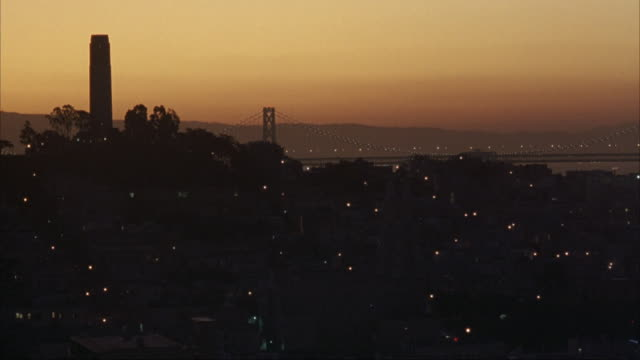 WIDE ANGLE OF TELEGRAPH HILL WITH COIT TOWER ON THE LEFT. SEE OAKLAND BAY BRIDGE IN BACKGROUND. SKY IS ORANGE FROM SUNSET. LANDMARKS.