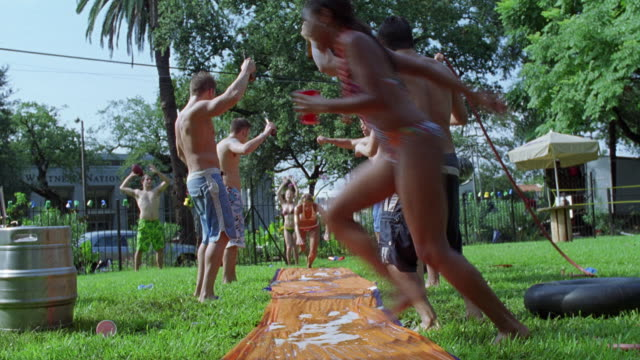 WIDE ANGLE OF PARTY IN FRONT YARD OF FRATERNITY HOUSE. COLLEGE AGE STUDENTS IN BATHING SUITS AND BIKINIS PLAYING ON SLIP N' SLIDE. BEER KEGS VISIBLE. COULD BE NEAR COLLEGE CAMPUSES.