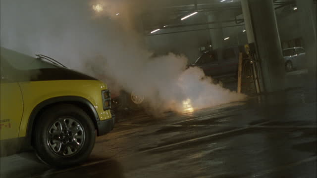 MEDIUM ANGLE OF YELLOW AND BLACK VAN, CAR, OR VEHICLE PARKED IN PARKING GARAGE OR STRUCTURE. SEE WHITE SMOKE OR STEAM RISING FROM GROUND AND FLAMES OF SMALL FLAMES ON GROUND. SEE METAL PIPES ON CONCRETE CEILING ABOVE.