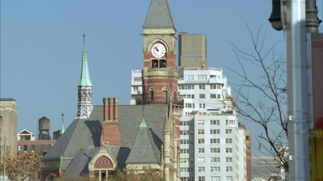 MEDIUM ANGLE OF TALL BUILDINGS, CROSSWALK SIGN, AND SIGN THAT READS TIME 10:52, PANS LEFT TO CLOCK TOWER, POSSIBLY ON CHURCH. PANS RIGHT TO BUILDINGS, THEN BACK RIGHT TO CLOCK TOWER. APARTMENT BUILDING IN BACKGROUND OF CLOCK TOWER.