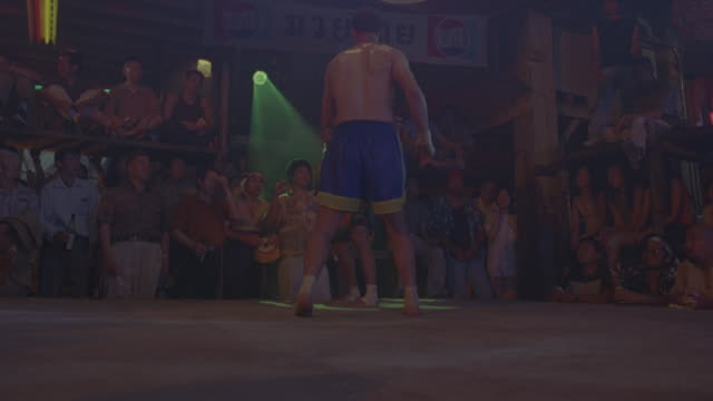 MEDIUM ANGLE OF STUNT OF TWO SHIRTLESS MEN FIGHTING IN  BOXING RING.  SEE AUDIENCE WATCHING FIGHT FROM BACK OF SHOT.  SEE MAN KICK BOX OTHER MAN IN THE FACE.  SEE OTHER MAN JUMP IN AIR, FLIP OVER, AND LAND ON STOMACH. 40 FPS SLOW MOTION. ACTION.