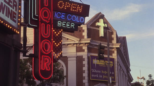ZOOM IN ON STREET CORNER WITH NEON SIGNS FOR LIQUOR STORE. LIQUOR, ICE COLD BEER, OPEN. CHURCH IN BACKGROUND WITH CRUCIFIX ABOVE BANNER THAT READS WHERE HOPE IS A WORK IN PROGRESS.