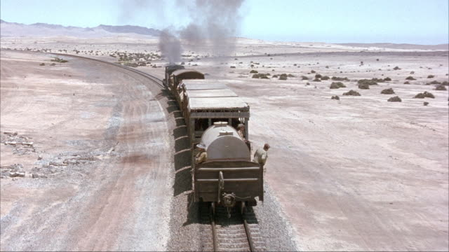 AERIAL OF STEAM ENGINE TRAIN TRAVELING DOWN RAILROAD TRACKS IN RURAL DESERT AREA. SEE MEN ON BACK CAR OF TRAIN WITH GUNS LOOKING OUT AT SURROUNDING LAND. SEE GREEN BUSHES AND SHRUBS LINE EITHER SIDE.