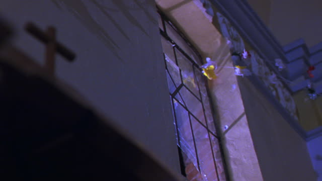 UP ANGLE OF CROSS IN CATHOLIC CHURCH. GREEN OBJECT FLIES THROUGH WINDOW BEHIND CROSS AND SHATTERS GLASS. SEE RED BRICK WALL OUTSIDE WINDOW.