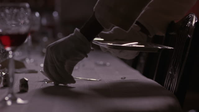 CLOSE ANGLE OF A PAIR OF HANDS IN WHITE GLOVES, PROBABLY FROM A SERVANT OR BUTLER.  THE HANDS PICK UP SILVERWARE AND BROKEN GLASS FROM THE FORMALLY SET DINING ROOM TABLE AND PLACE THEM ON A SILVER TRAY.