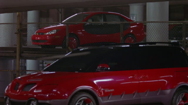 MEDIUM ANGLE OF PARKING STRUCTURE OR PARKING GARAGE. CONCRETE WALLS AND CEILING. GARAGE IS MOSTLY EMPTY. FUTURISTIC RED CARS PARKED ON TWO LEVELS. CAMERA TRACKS GREEN VW VOLKSWAGEN NEW BEETLE CAR AS IT SPEEDS THROUGH GARAGE.
