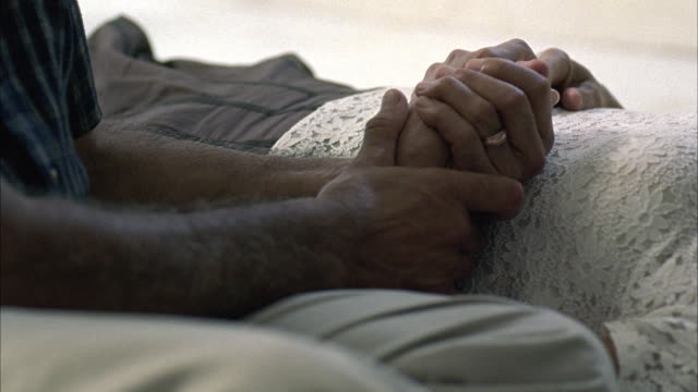 CLOSE ANGLE OF ARM OF ELDERLY WOMAN IN HOSPITAL BED. ELDERLY MAN RUBS HER HAND. PAN UP TO THE MAN LOOKING AT THE PATIENT.