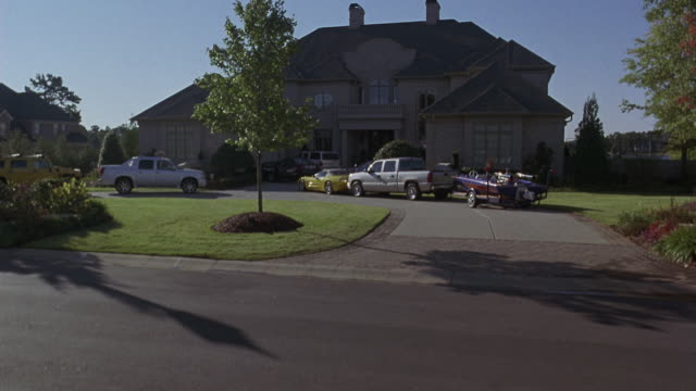 PAN UP TO SHOW LARGE MANSION HOUSE  WITH SURROUNDING MANICURED LAWN, WITH TREES AND LAKE IN BACKGROUND. HOUSE IS LARGE AND GRAY WITH SLATE ROOF. SEVERAL CARS ARE PARKED IN LARGE DRIVEWAY IN FRONT OF HOUSE, INCLUDING TRUCKS, CARS, MUSCLE CARS, AND A BOAT.
