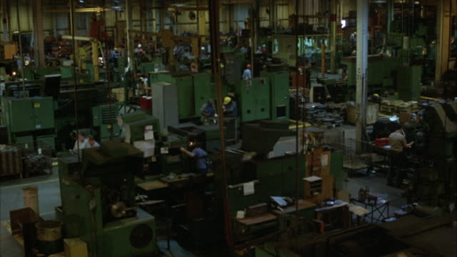 HIGH ANGLE DOWN OF WORKERS ON FACTORY FLOOR. COULD BE MACHINE SHOP OR PLANT. SEE WORKERS IN HARDHATS AND WORK SHIRTS MOVING ABOUT. SEE VARIOUS MACHINERY ON FLOOR. SHOT PANS LEFT A LITTLE.