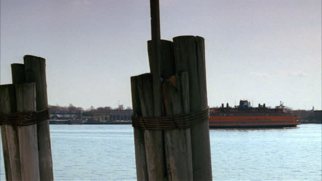 MEDIUM ANGLE OF STATEN ISLAND FERRY ON HUDSON RIVER. WOODEN POLES ON DOCK OBSCURE AT FIRST, BUT PANS LEFT TO TRACK FERRY SLOW, STOP, AND REVERSE. SIGN AT RIGHT SAYS GANGWAY 2.