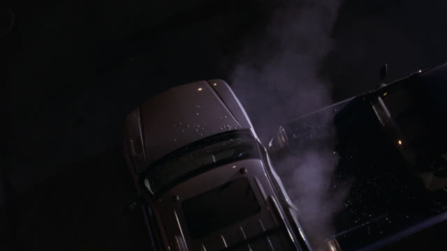 HIGH ANGLE DOWN BIRDSEYE POV OF CAR ACCIDENT OR CAR CRASH BETWEEN PICKUP TRUCK AND COMPACT CAR. BROKEN GLASS AND SMOKE VISIBLE. BIZBARS OR FLASHING LIGHTS FROM POLICE CAR REFLECT OFF VEHICLES.