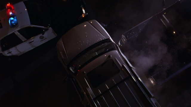 HIGH ANGLE DOWN BIRDSEYE POV OF POLICE CAR WITH FLASHING LIGHTS OR BIZBARS AND CAR ACCIDENT OR CAR CRASH BETWEEN PICKUP TRUCK AND COMPACT CAR. BROKEN GLASS AND SMOKE VISIBLE.