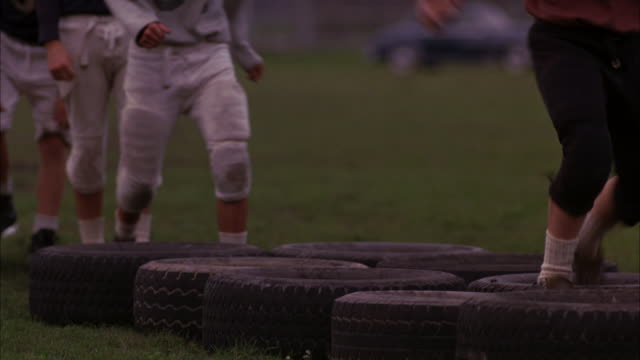 MEDIUM ANGLE OF A FOOTBALL TEAM PRACTICING ON A FIELD WEARING OLD FASHIONED HELMETS. THE YOUNG MEN RUN THROUGH AN OBSTACLE COURSE MADE OF TIRES. STADIUMS, FIELDS, UNIFORMS.
