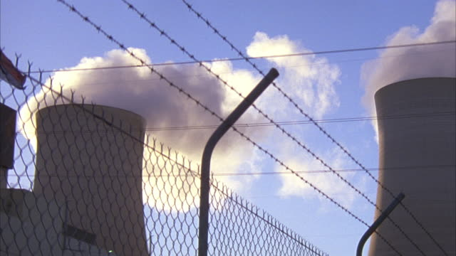 WIDE ANGLE OF BARBED WIRE FENCE AROUND  NUCLEAR POWER PLANT. SEE TWO COOLING TOWERS SPEWING STEAM INTO CLEAR BLUE SKY. SEE LARGE RECTANGULAR BUILDING NEXT TO COOLING TOWERS- COULD BE REACTOR BUIDLING. SEE RUSSIAN FLAG.