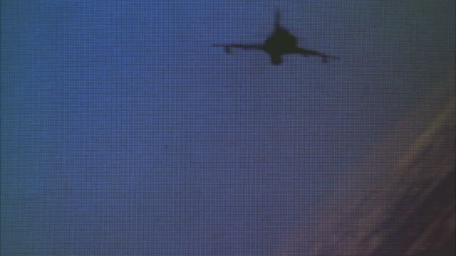 MEDIUM ANGLE OF F-16 FIGHTER JET FLYING AWAY FROM CAMERA IN BANKED RIGHT TURN. DESERT VISIBLE IN BACKGROUND. MIDDLE EAST.