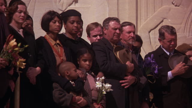 MEDIUM ANGLE OF MOURNERS AT FRONT OF CAPITOL BUILDING IN BATON ROUGE, LOUISIANA. COULD BE STATE FUNERAL. GOVERNMENT BUILDINGS. WOMEN, CHILDREN HOLD FLOWERS, MEN HOLD HATS OVER THEIR HEARTS.